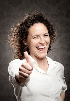 Happy business woman giving a thumbs up sign