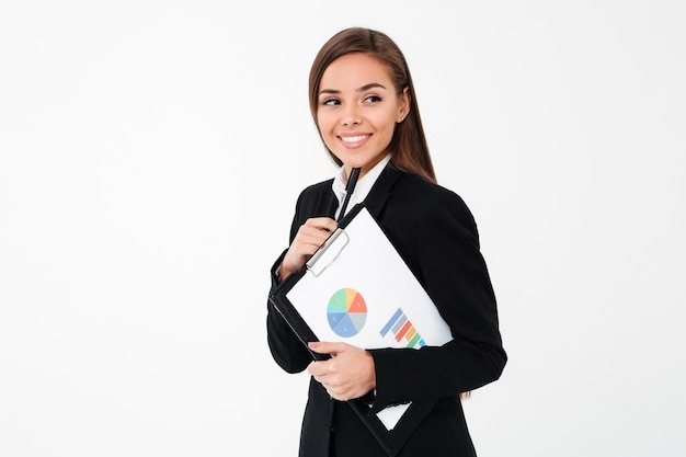 Happy business woman holding clipboard. looking aside.