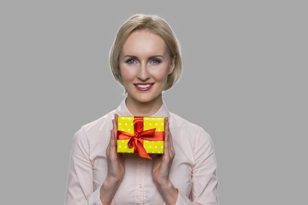 Счастливая бизнес-леди держа подарочную коробку обеими руками. довольно улыбается женщина позирует с небольшой подарочной коробке в руках на сером фоне.