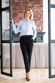 Happy business woman holding hand in pocket