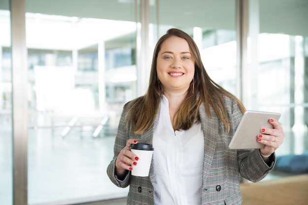 Happy business woman holding tablet and coffee outdoors