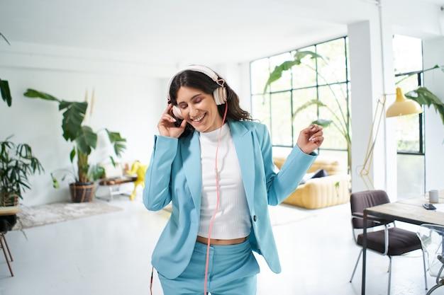 フォーマルなスーツのダンスで幸せなビジネスウーマンは、オフィスでの仕事の成功を祝う動機を持っています...