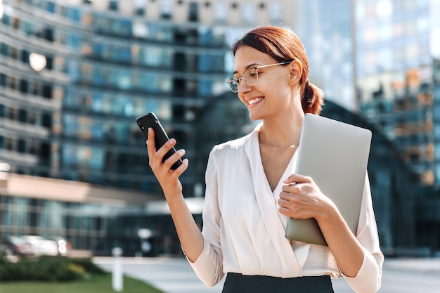 Счастливая деловая женщина в очках держит ноутбук и использует телефон на открытом воздухе в современном городе