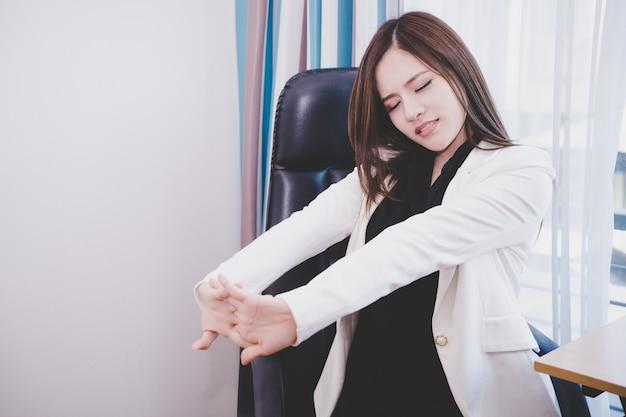 幸せなビジネス女性は、リラックスして、オフィスで伸びている