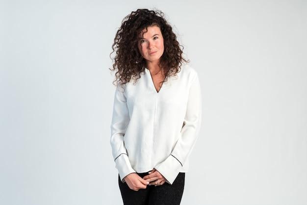 穏やかな顔でカメラを見て、腰で腕を組んで幸せなビジネス女性。白い背景で隔離。ストックフォト