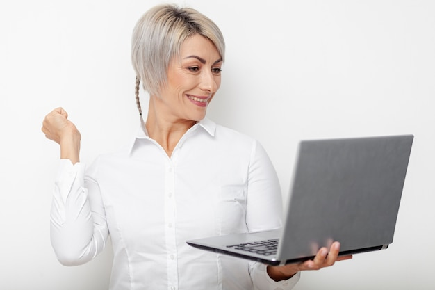 Happy business woman looking on laptop