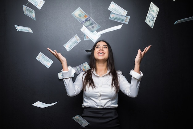 Happy business woman under a money rain made of dollars isolated on black wall