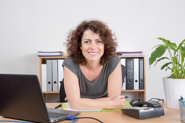 Happy business woman at the office smiling with arms on table