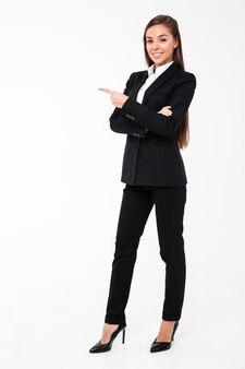 Счастливая бизнес-леди указывая к copyspace.