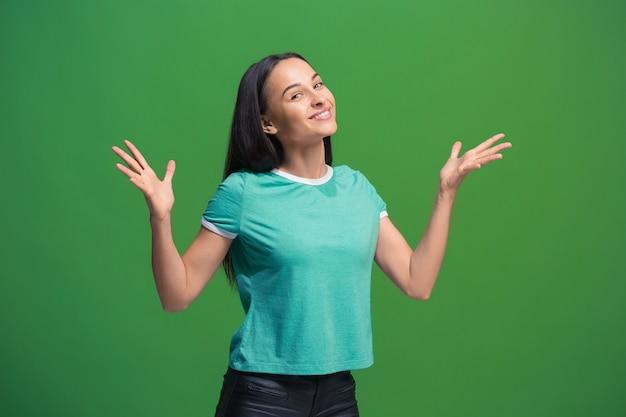 緑のスタジオの背景に孤立して立って笑顔幸せなビジネス女性。美しい女性の半身像。若い感情的な女性。人間の感情、表情のコンセプト。正面図。