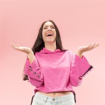 ピンクのスタジオの背景に孤立して立って笑顔幸せなビジネス女性。美しい女性のハーフレングスの肖像画。若い感情的な女性。人間の感情、表情の概念