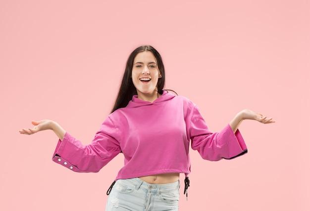 ピンクのスタジオの背景に孤立して立って笑顔幸せなビジネス女性。美しい女性の半身像。