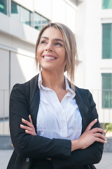 Happy business woman standing outdoors
