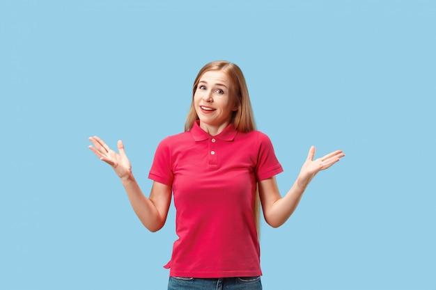 La donna felice di affari che sta e che sorride contro la parete blu