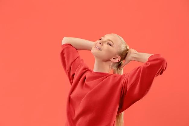 Счастливая деловая женщина стоя, улыбаясь изолированной на стене модной коралловой студии