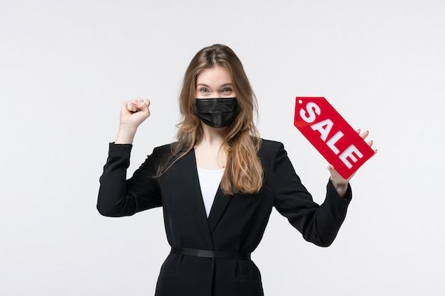 Donna d'affari felice in tuta che indossa la sua maschera medica e mostra vendita su bianco isolato