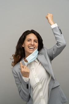 Счастливая деловая женщина снимает маску, поднимает кулак, студия, covid-19 закончился. пандемия закончилась.