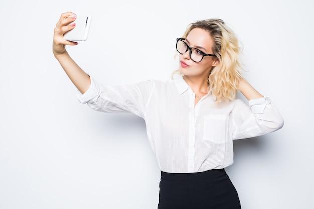 白で隔離自撮り写真スマートフォンを撮って幸せなビジネス女性。衣装を着た女性のビジネスモデル。
