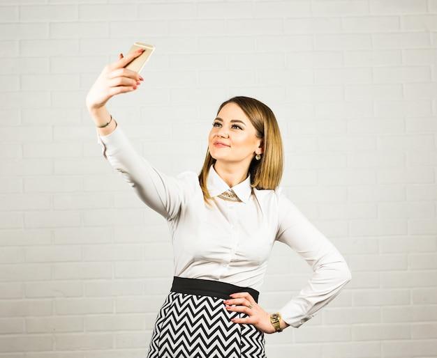 Selfie写真のスマートフォンを取って幸せなビジネスの女性。テクノロジーと人々のコンセプト