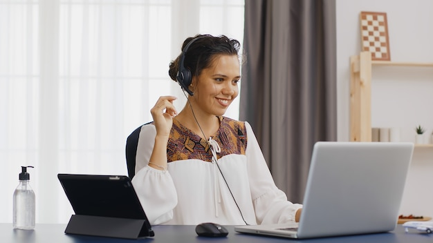 Счастливая деловая женщина в наушниках во время видеозвонка во время работы из домашнего офиса.