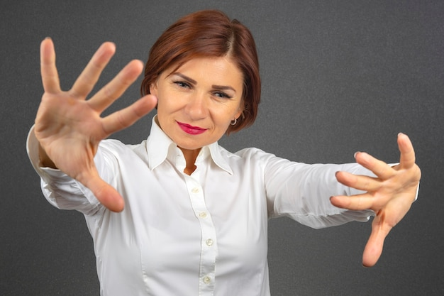 Happy business woman in a white shirt with arms outstretched.