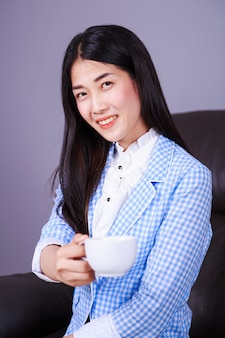 Happy business woman with coffee or tea cup