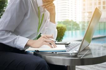 屋外でノートパソコンとノートブックで働くハッピービジネスの女性