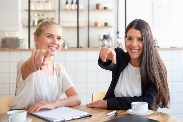 コーヒーカップとドキュメントとテーブルに座っている間カメラでポーズをとって指を指している幸せなビジネス女性