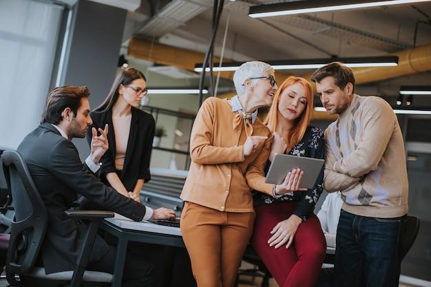 オフィスで若いチームの前でデジタルタブレットでオンラインで一緒に働く幸せなビジネス女性