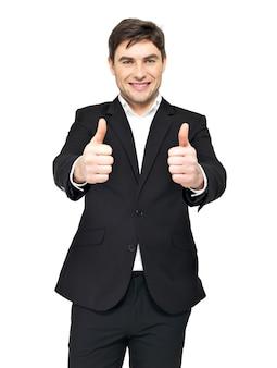 L'uomo d'affari felice in vestito nero mostra i pollici sul segno isolato su bianco.