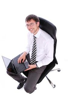 Uomo d'affari felice sulla sedia con il computer portatile