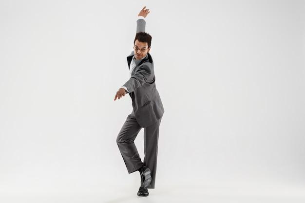 Счастливый бизнесмен, танцы в движении, изолированные на белом фоне студии. гибкость и изящество в бизнесе. концепция человеческих эмоций. офис, успех, профессионализм, счастье, концепции выражения