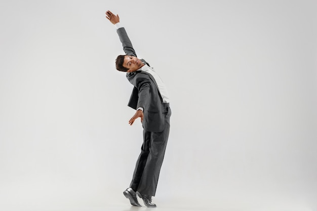 白いスタジオの背景に分離された動きで踊る幸せな実業家。ビジネスにおける柔軟性と優雅さ。人間の感情の概念。オフィス、成功、専門家、幸福、表現の概念