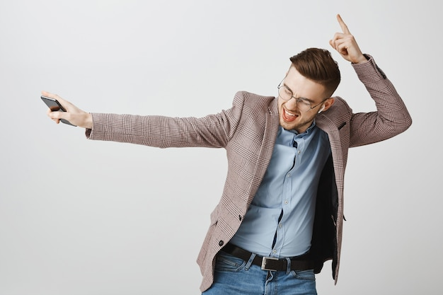 スマートフォンで喜んで踊る幸せなビジネスマン、ワイヤレスイヤホンで音楽を聴く