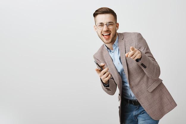 Счастливый бизнесмен танцует в радости со смартфоном, слушая музыку в беспроводных наушниках