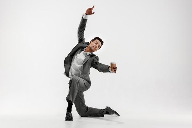 Uomo d'affari felice ballando in movimento isolato su sfondo bianco studio. flessibilità e grazia negli affari. concetto di emozioni umane. ufficio, successo, professionale, felicità, concetti di espressione