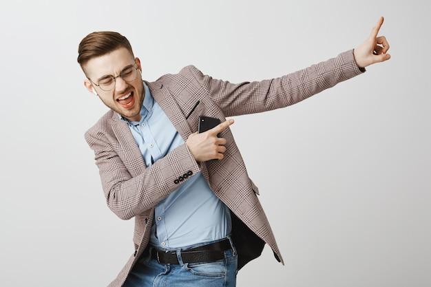 Felice imprenditore ballando in gioia con lo smartphone, ascoltando musica in auricolari wireless
