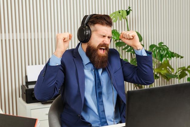 腕を上げて勝者のジェスチャーをしている幸せな実業家。成功を叫ぶ興奮したあごひげを生やした男。スーツとヘッドセットを身に着けているビジネスマン。成功を祝う。