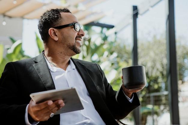 Счастливый бизнесмен, наслаждаясь кофе во время использования планшета