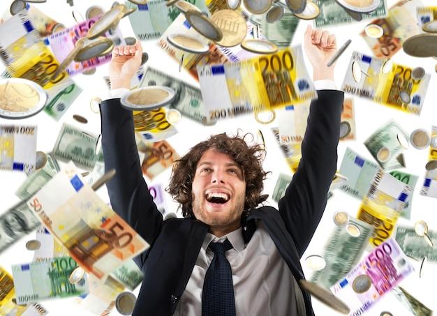 幸せなビジネスマンは、コインや紙幣の雨の下で歓喜します
