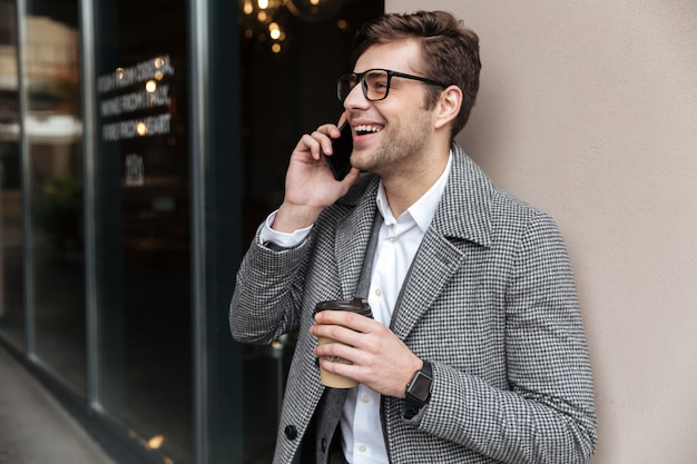 Happy businessman in eyeglasses and coat talking by smartphone