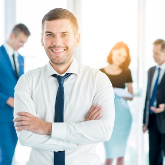 Happy businessman folding his arms with is colleagues in background