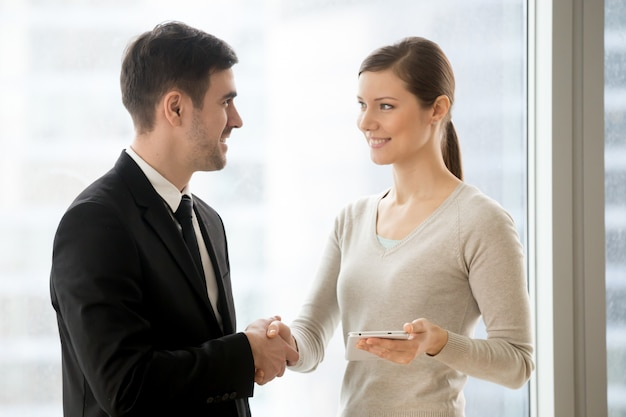 Happy businessman handshaking smiling businesswoman