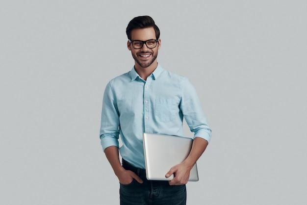 幸せなビジネスマン。ラップトップを携帯し、灰色の背景に立ってカメラを見ているハンサムな若い男