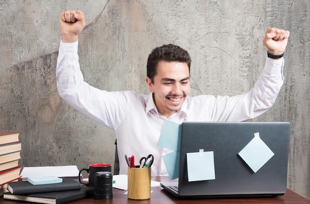 オフィスデスクで最高の瞬間を持っている幸せなビジネスマン。