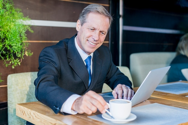 Happy businessman having cup of coffee with laptop on desk in caf�