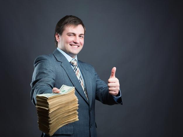 お金の大きなパックを保持している幸せな実業家