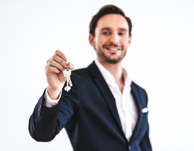 The happy businessman holding keys on the white background
