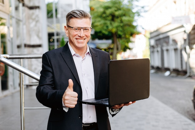 Happy businessman holding open laptop, smiling with thumb up