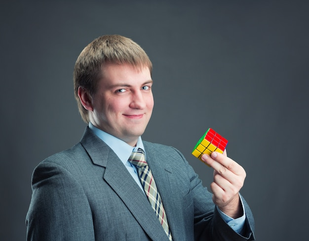Happy businessman holding rubik cube in his hands